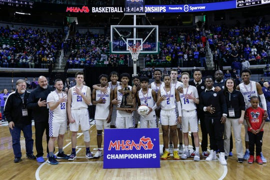 Southfield Christian players and coach staff pose for a photo with MHSAA Division 4 championship trophy at the Breslin Center in East Lansing, Saturday, March 16, 2019.