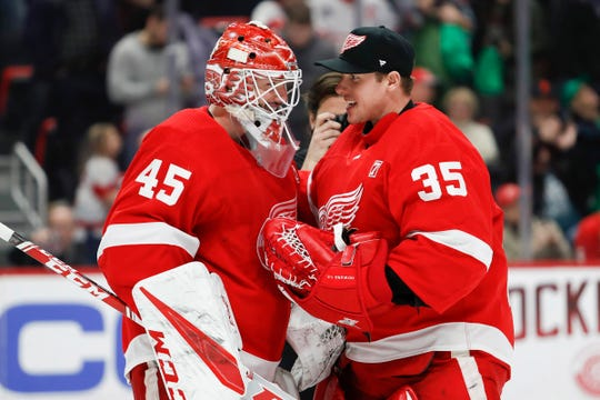 Red Wings goaltender Jonathan Bernier celebrates with goaltender Jimmy Howard after the Wings' 2-1 win on Saturday, March 16, 2019, at Little Caesars Arena.