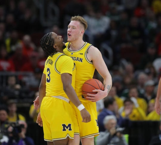 Zavier Simpson, left, and Ignas Brazdeikis celebrate a basket against Minnesota on Saturday in Chicago.
