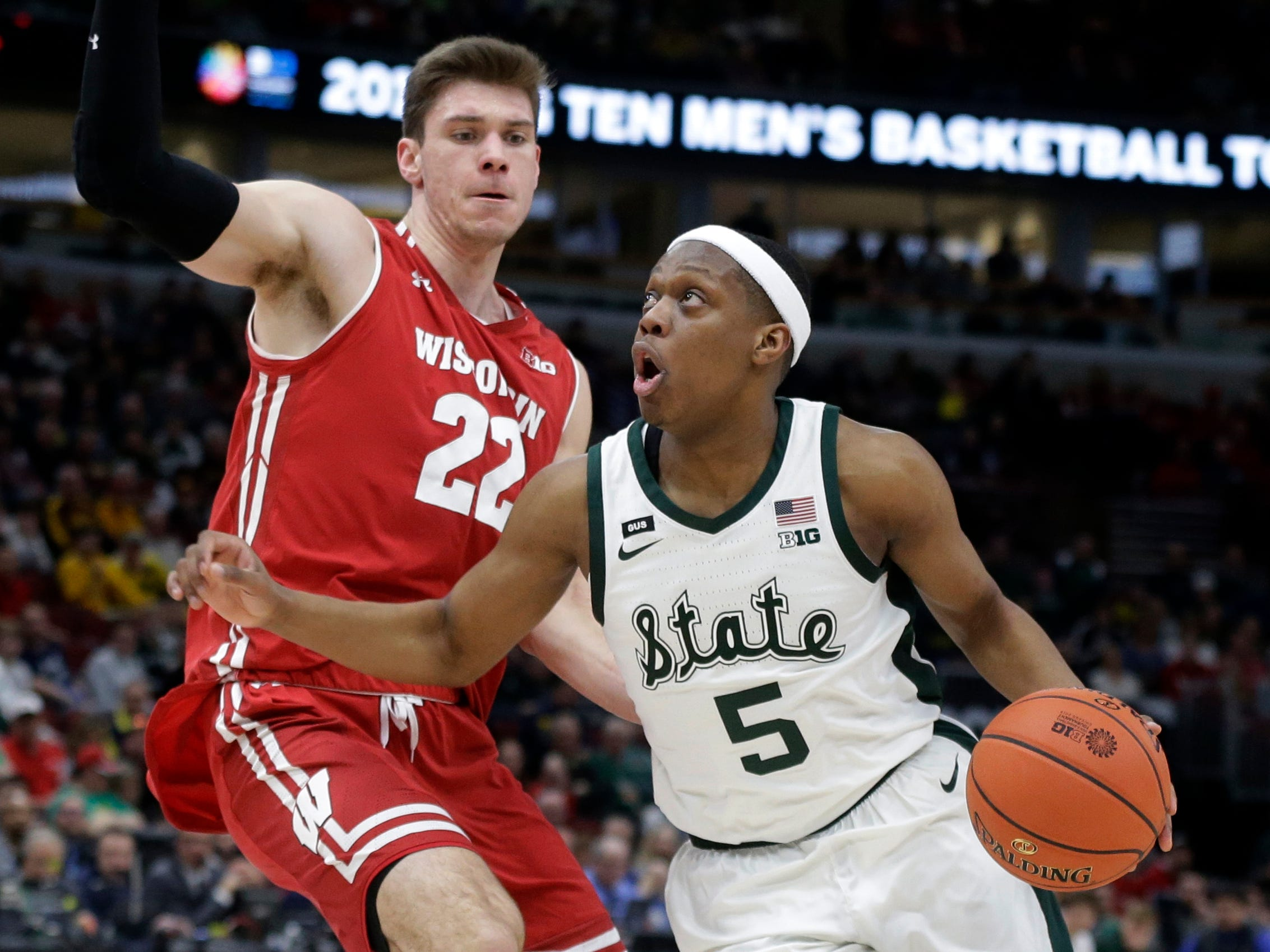 Michigan State's Cassius Winston drives past Wisconsin's Ethan Happ during the first half.