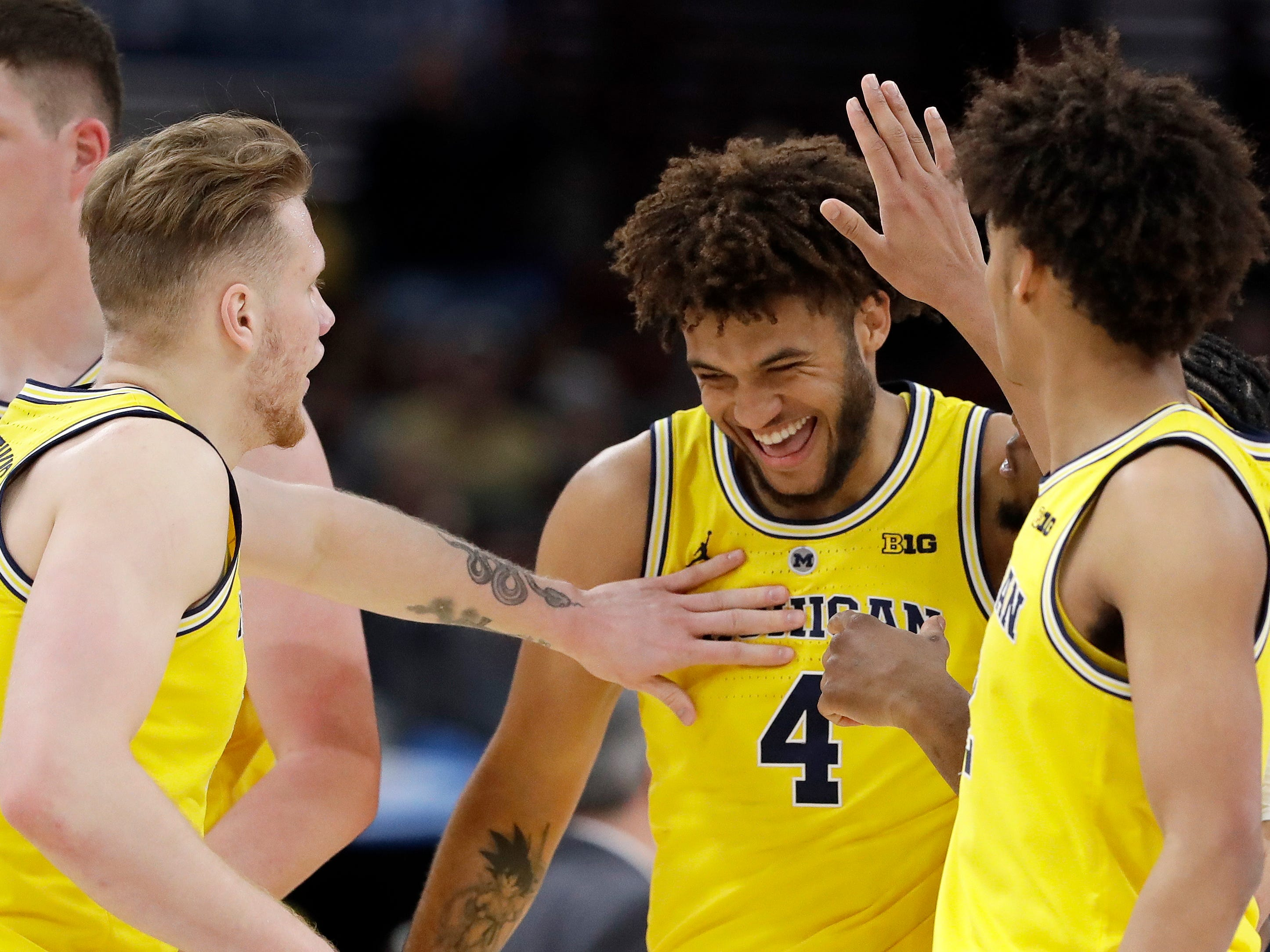 Michigan's Isaiah Livers is congratulated by his teammates after a dunk in Saturday's win over Minnesota.