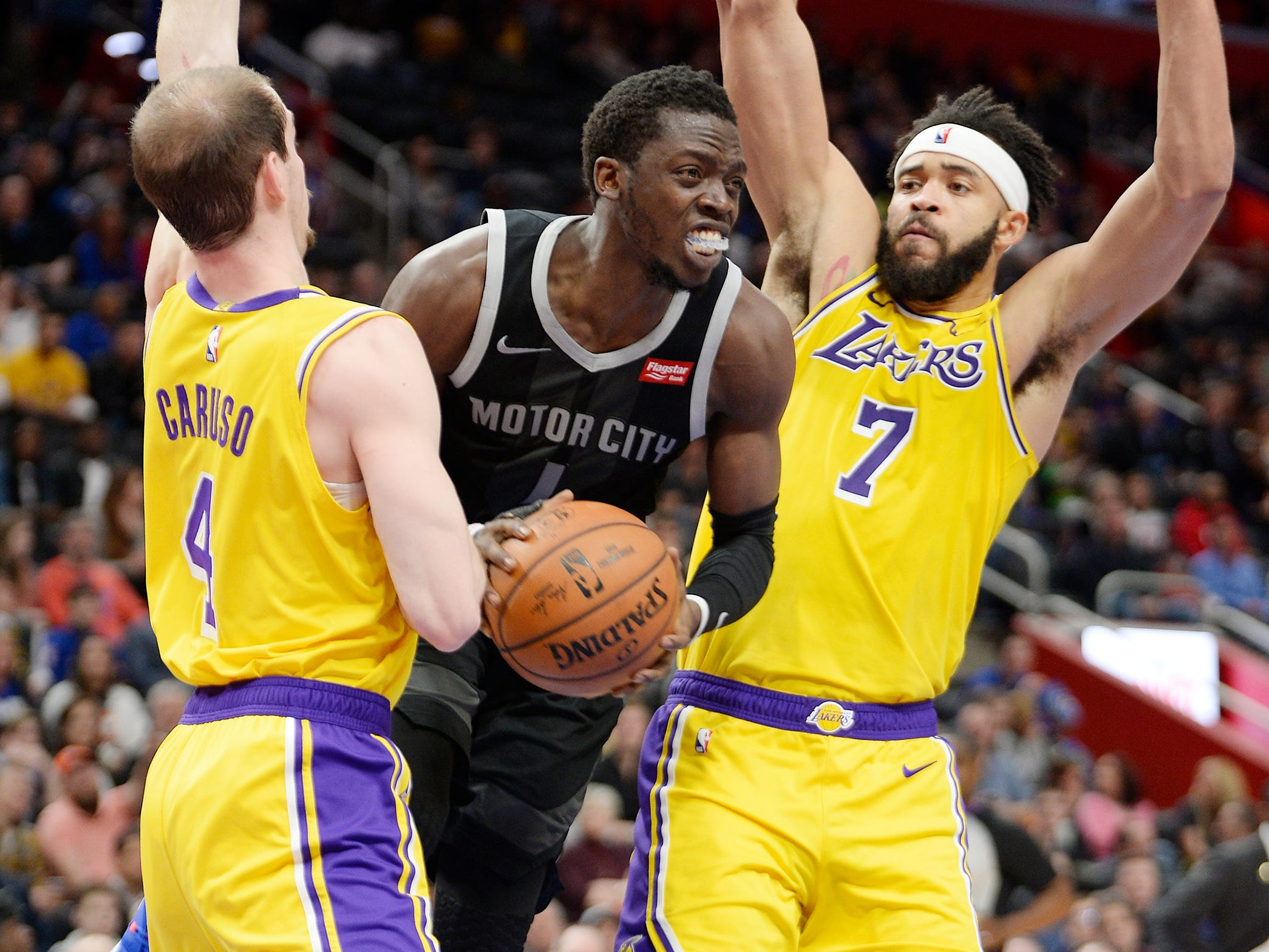 Pistons' Reggie Jackson is fouled by Lakers' Alex Caruso, (l), in the second quarter.
