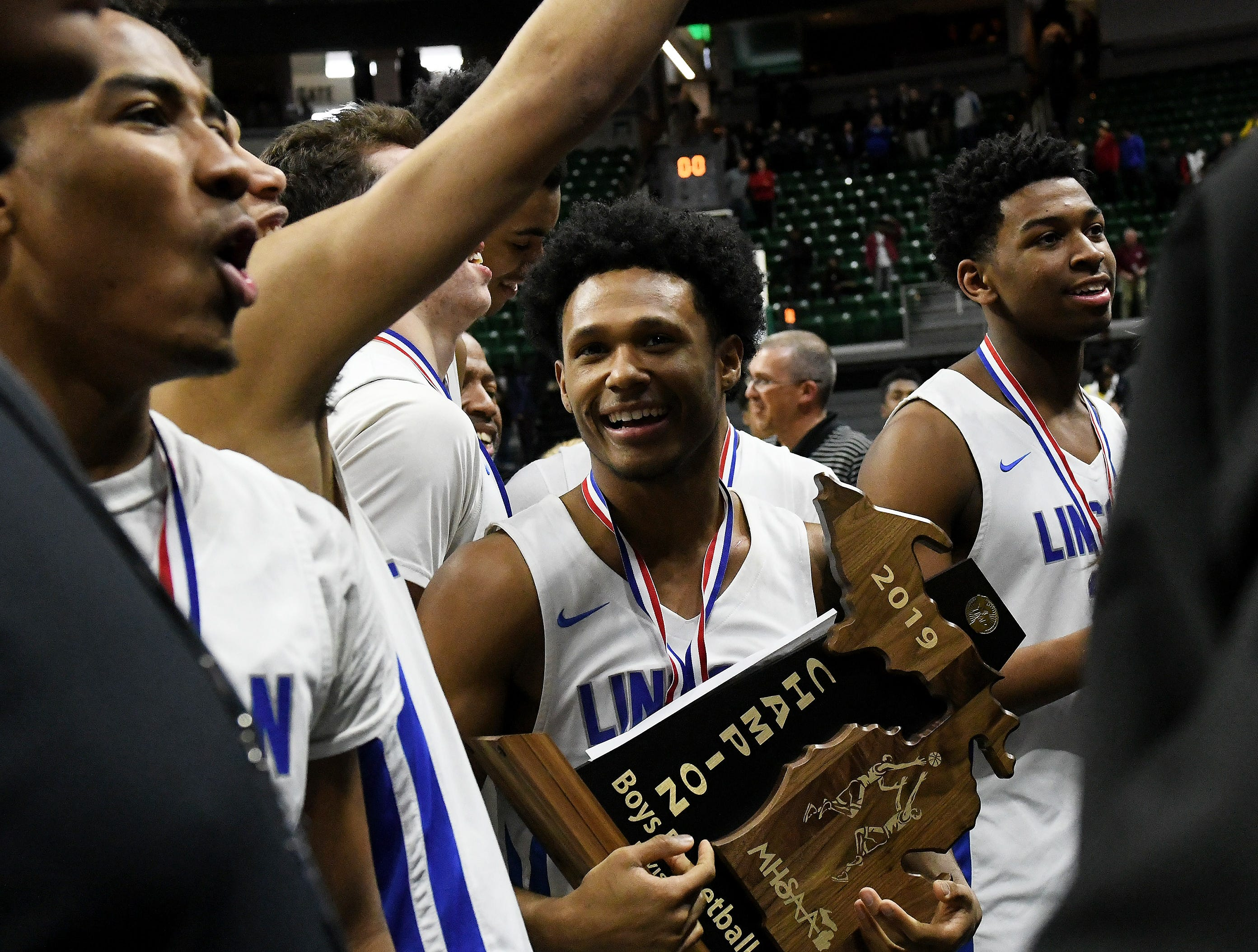 Lincoln guard Jalen Fisher (14), who hit the game-winner, holds the trophy.