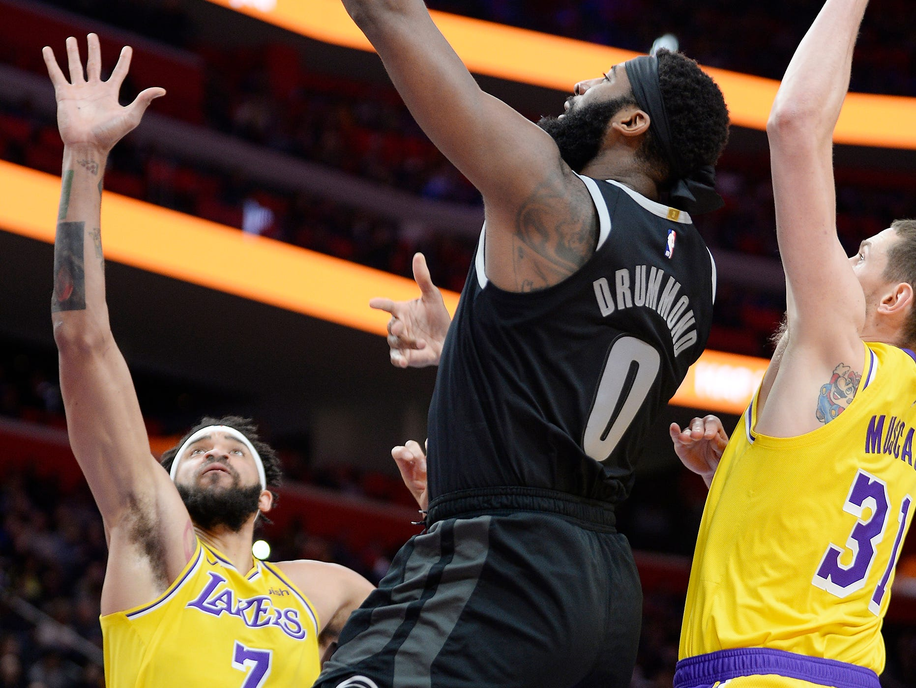 Pistons' Andre Drummond shoots over Lakers' JaVale McGee, (l), and Mike Muscala in the first quarter. Drummond had 19 points and 23 rebounds.
