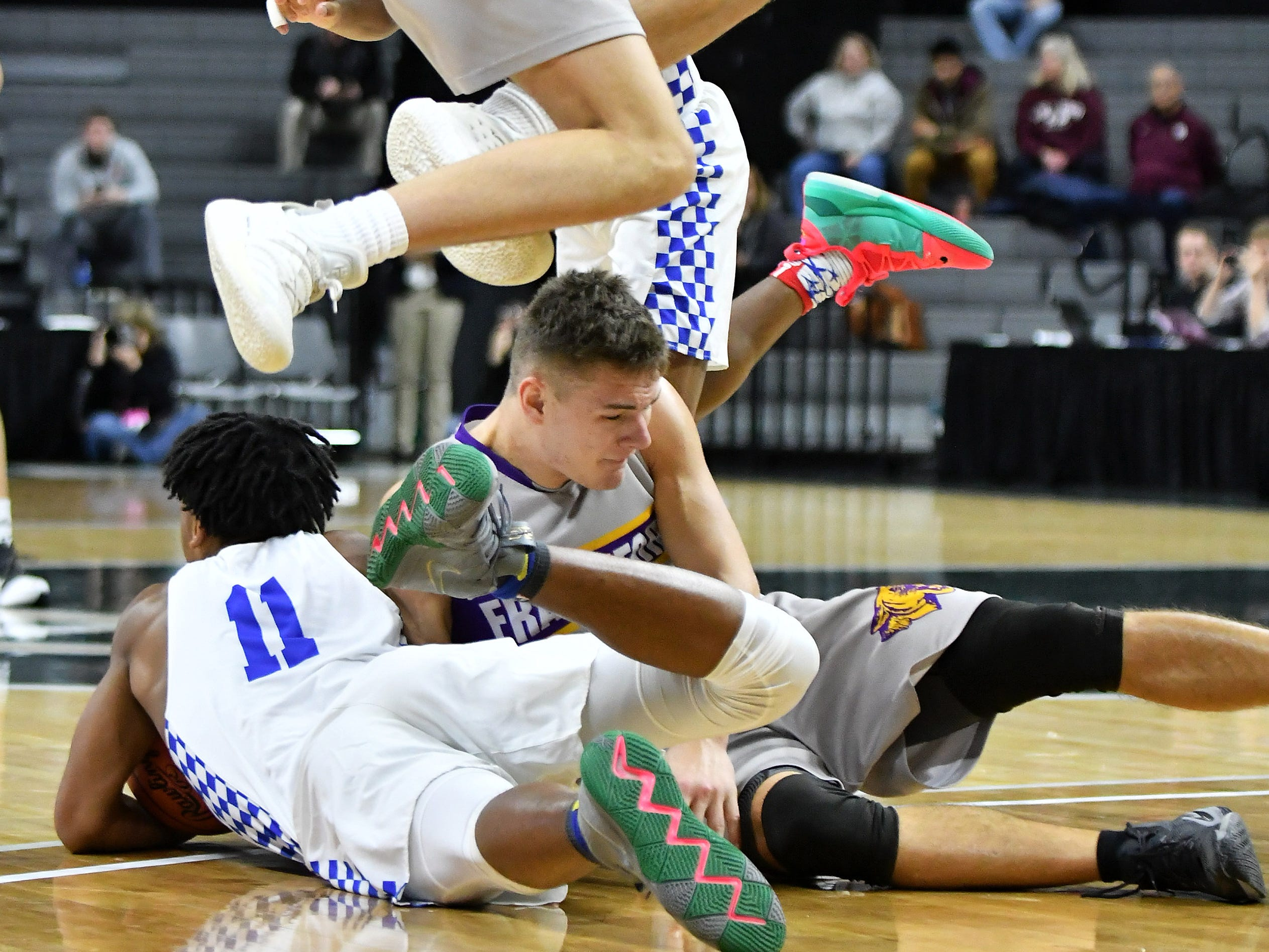 Frankfort forward Luke Hammon hops over Southfield Christian forward Malcolm King battling for a loose ball in the first half.