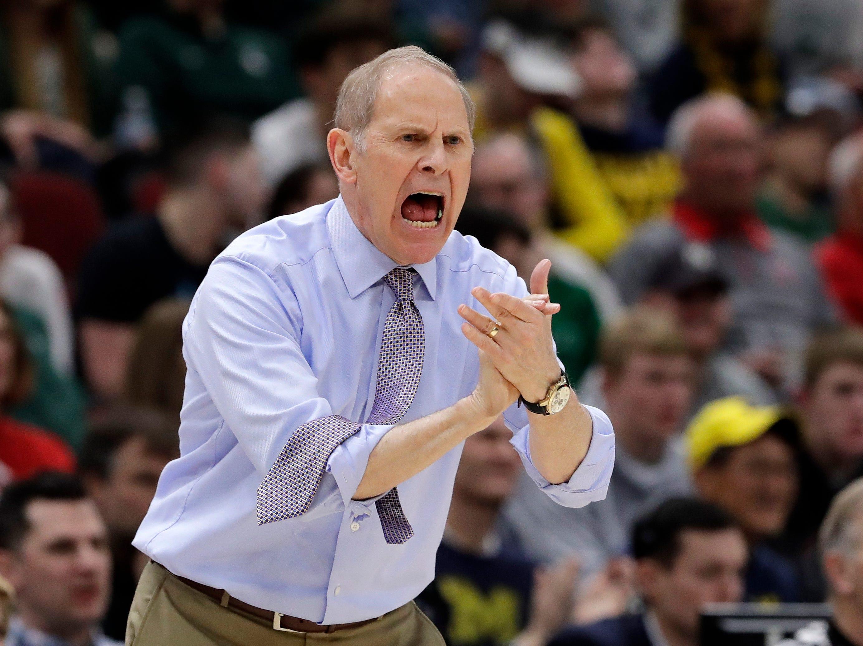 Michigan head coach John Beilein directs his team during the first half.