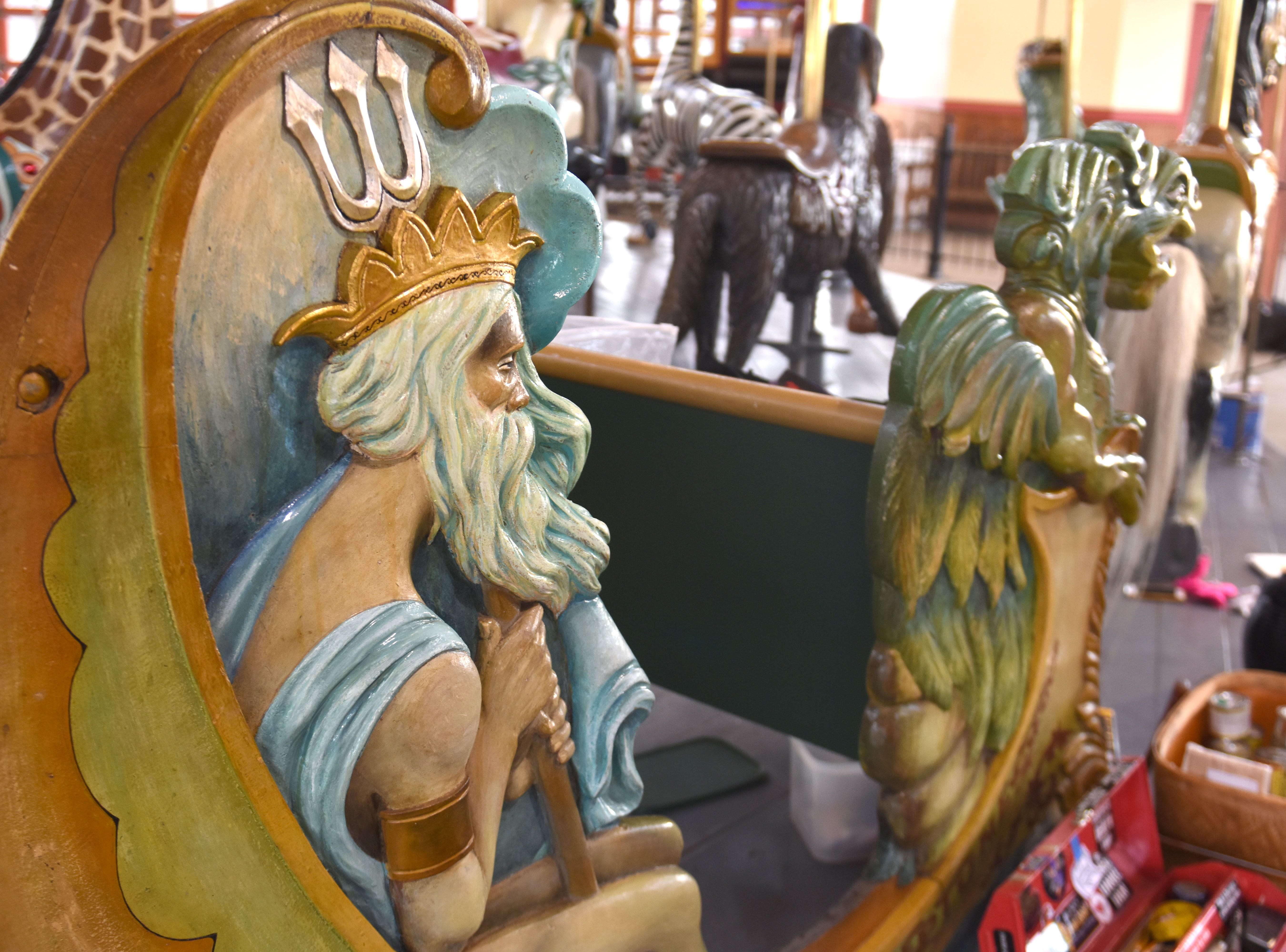 Craved wooden figures are carefully painted during Julie Fournier restoration.