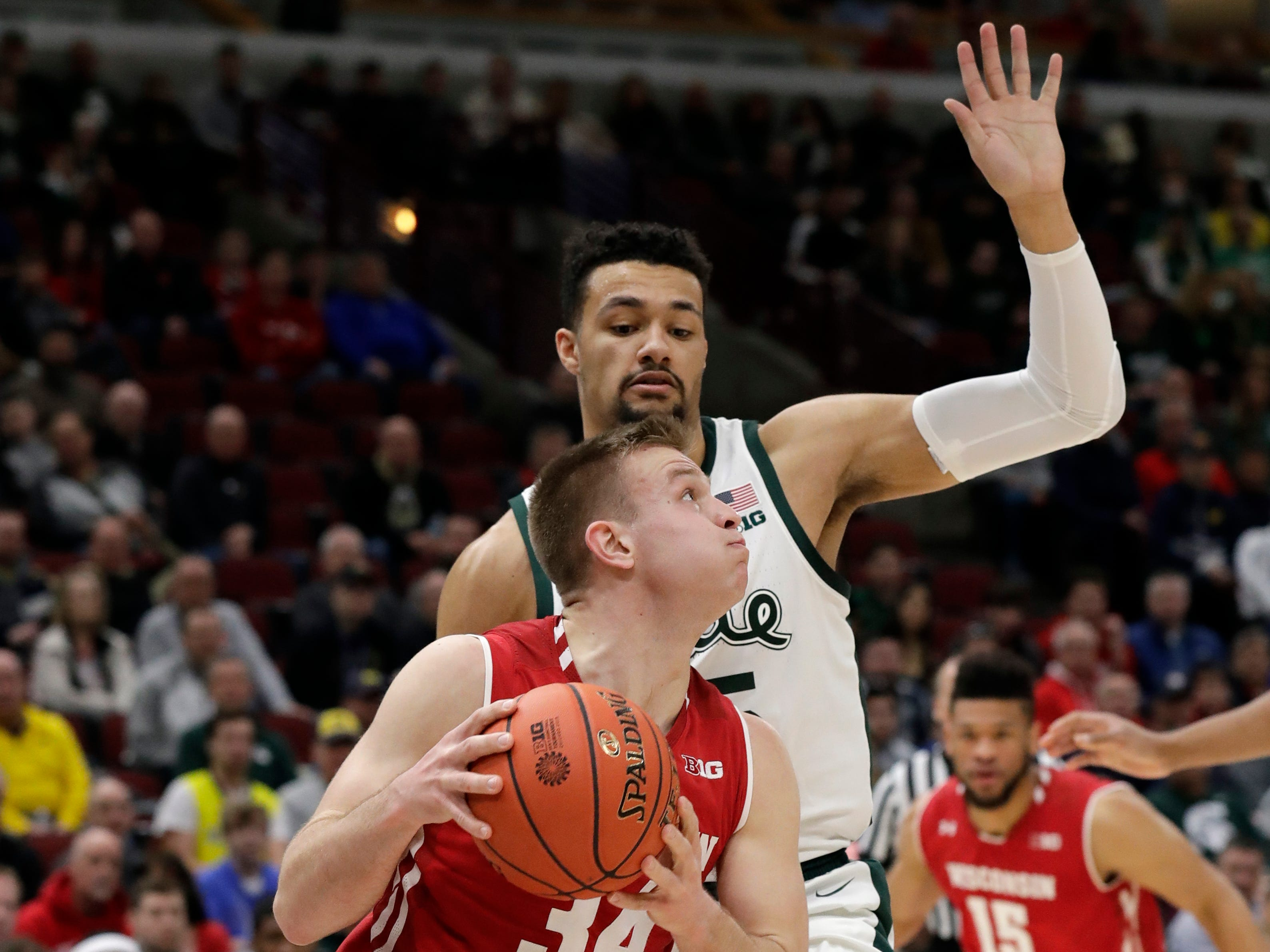 Wisconsin's Carter Higginbottom drives against Michigan State's Kenny Goins during the first half.