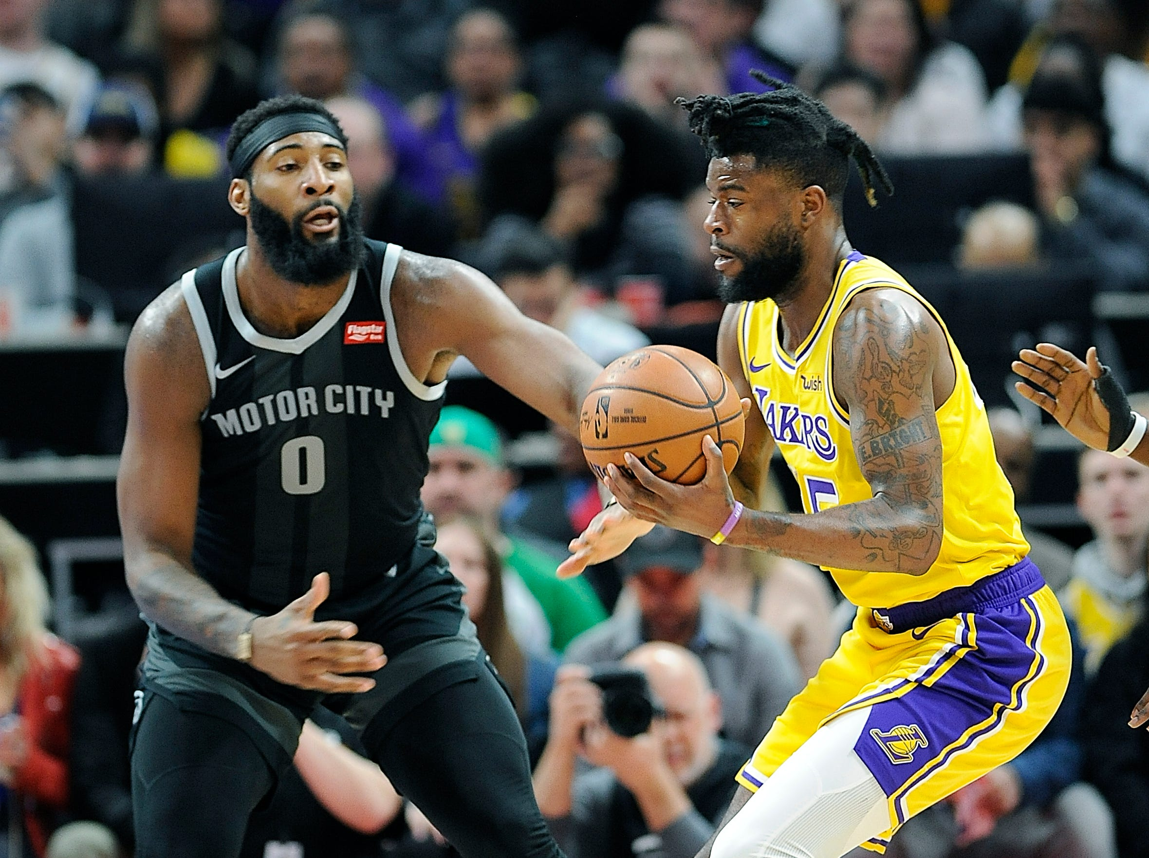 Pistons' Andre Drummond defends Lakers' Reggie Bullock in the first quarter.