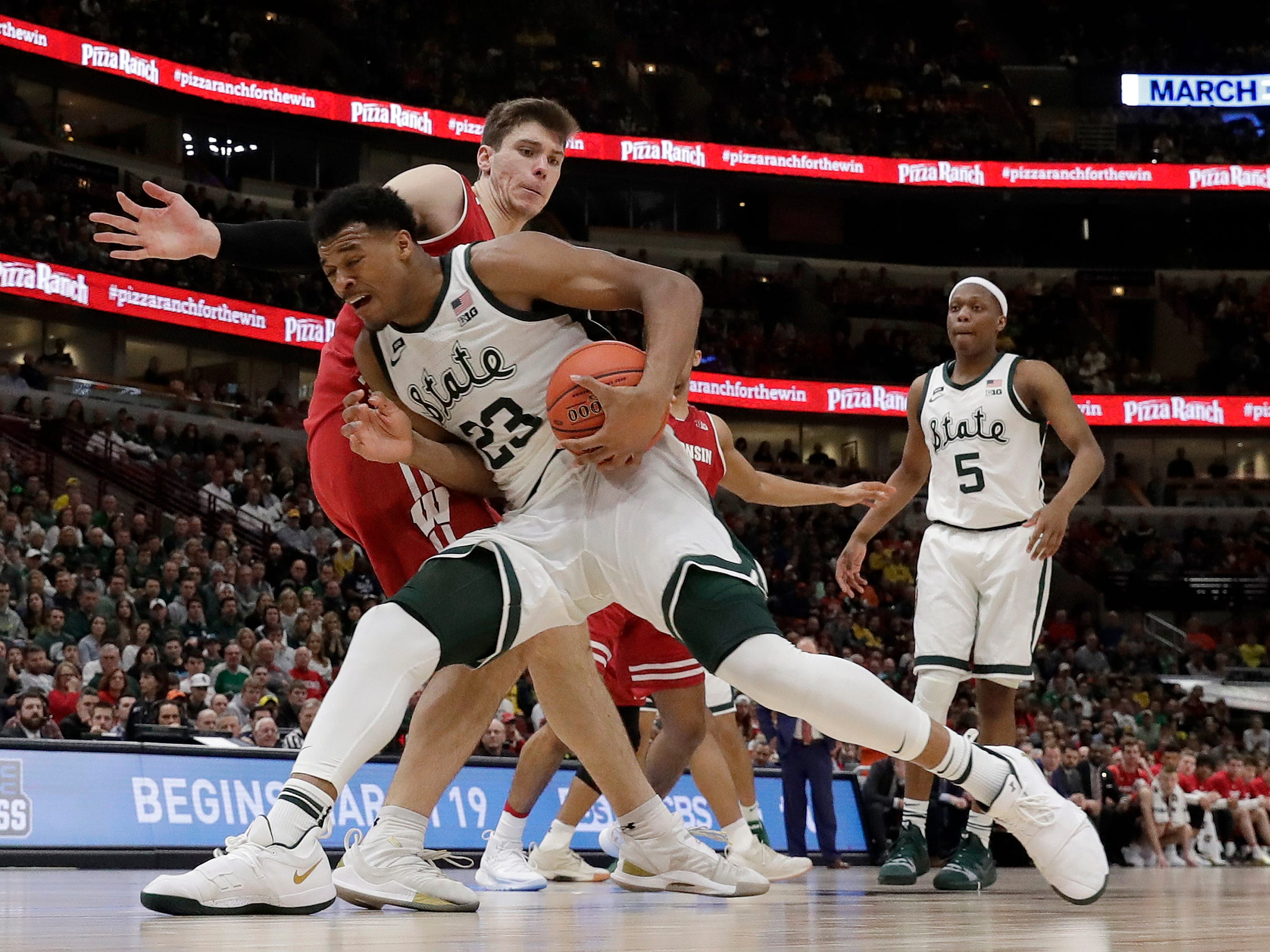 Michigan State's Xavier Tillman drives against Wisconsin's Ethan Happ during the second half.