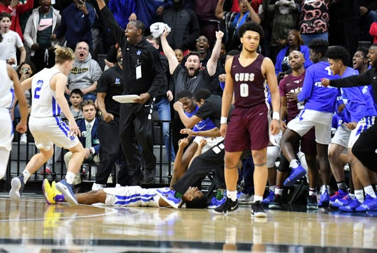 Ypsilanti Lincoln guard Jalen Fisher, on the floor, reacts after hitting the winning shot at the buzzer in a 64-62 victory over U-D Jesuit in the Division 1 final Saturday.