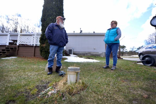 Mike and Sabrina Shafer stand by their well in the backyard of their Grand Haven home. The Shafers fear that they may be affected by PFAS contaminated well water. The water at Robinson school across the street has tested positive for PFAS contamination.