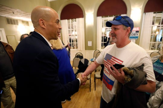 2020 Democratic presidential candidate Sen. Cory Booker talks with John Pforr, of Fairfield, Iowa, right, during a meeting with local residents, Saturday, March 16, 2019, in Ottumwa, Iowa.