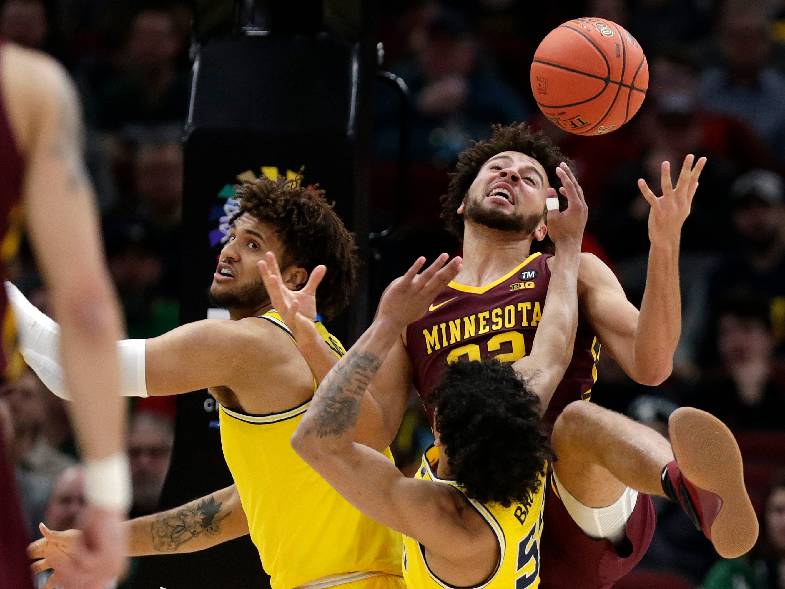 Minnesota's Gabe Kalscheur, right, battles for a rebound against Michigan's Eli Brooks and Isaiah Livers, left, during the first half.