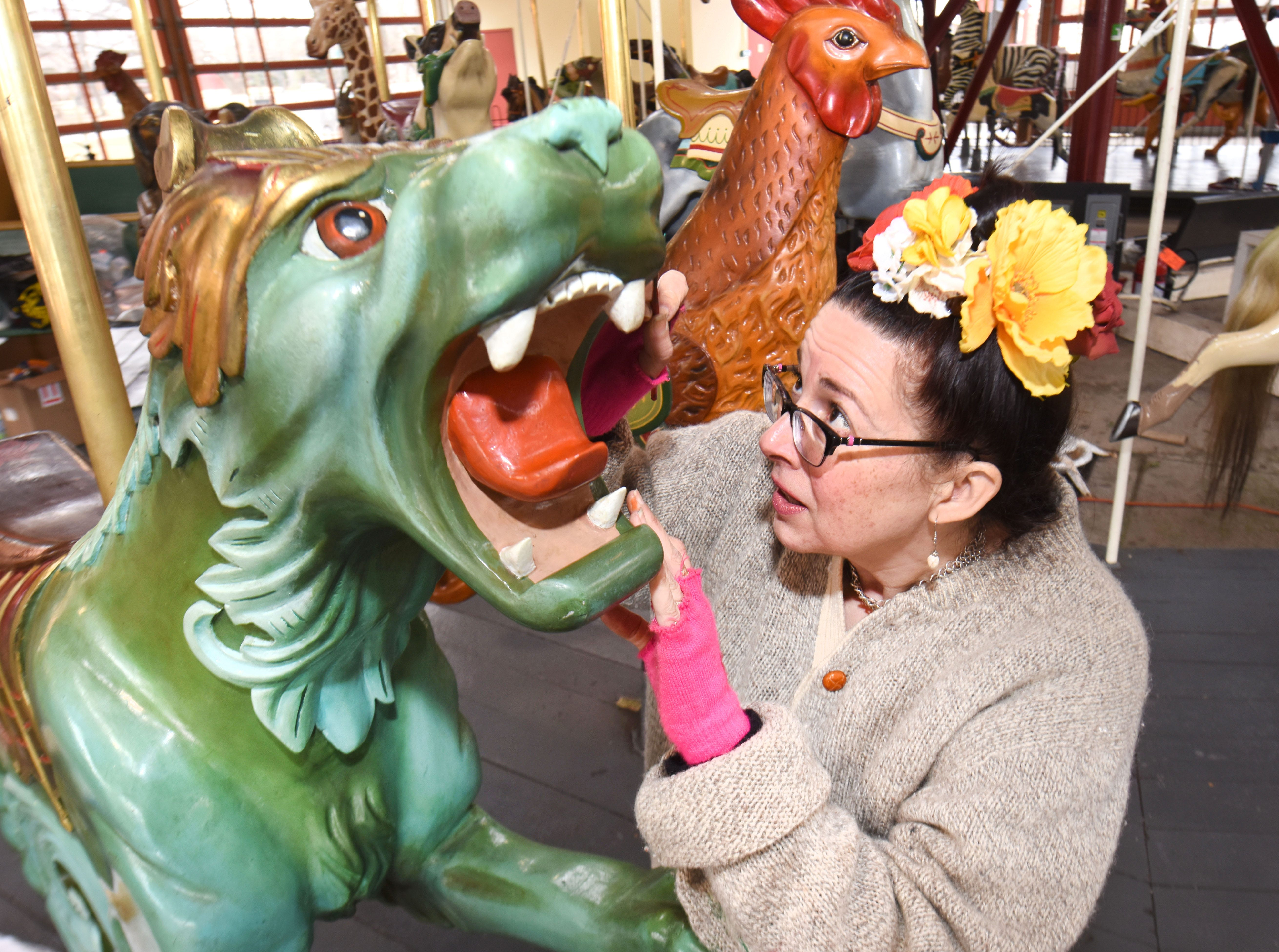 Julie Fournier, historic restoration artist,  works  on one of her favorite carousel  figure's, a dragon, at Greenfield Village in Dearborn on Thursday, March 14, 2019.