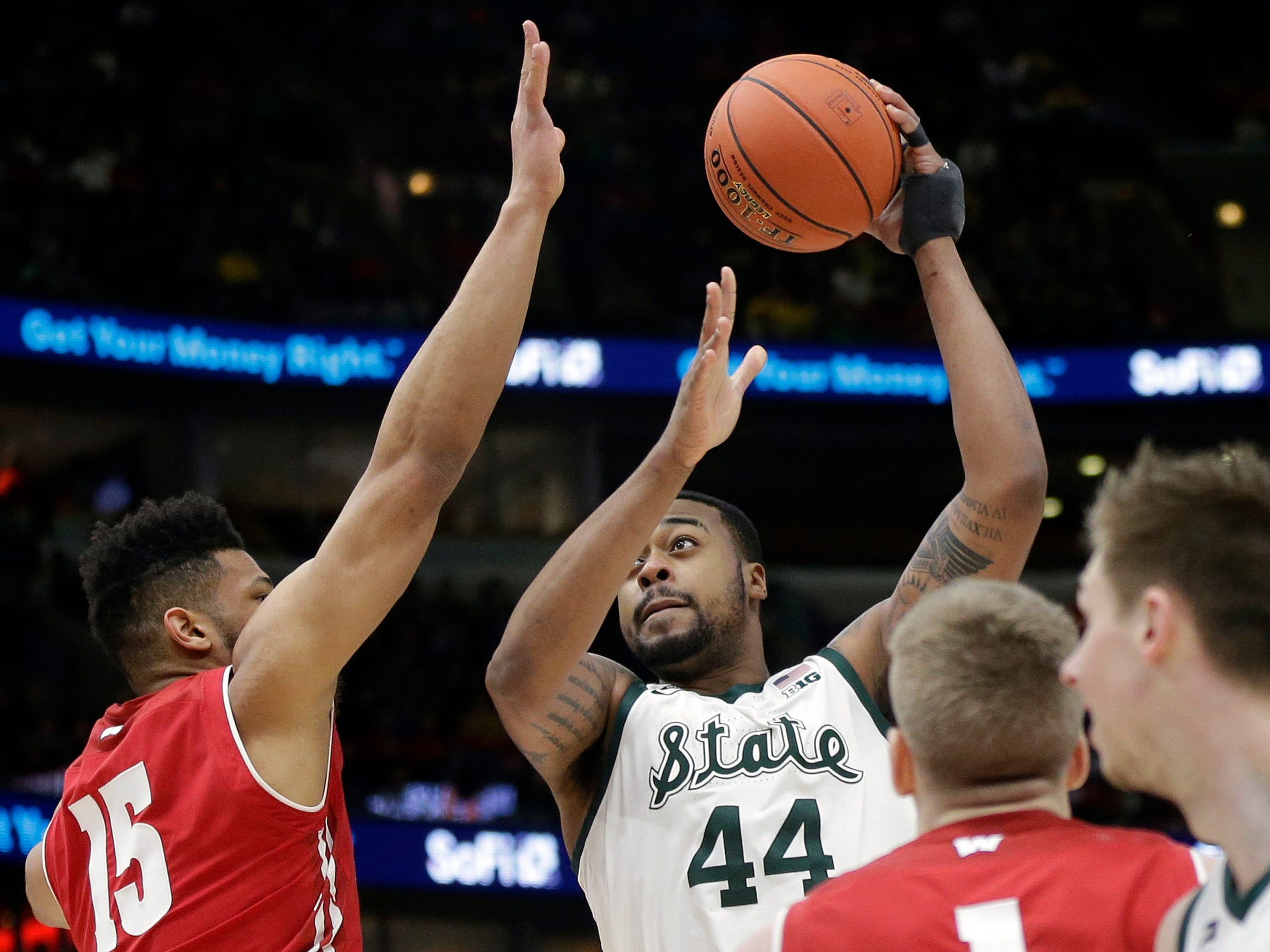 Michigan State's Nick Ward takes a shot over Wisconsin's Charles Thomas IV (15) during the first half.