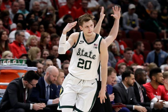 Michigan State's Matt McQuaid reacts after shooting a 3-point basket in the first half of the game against Wisconsin.