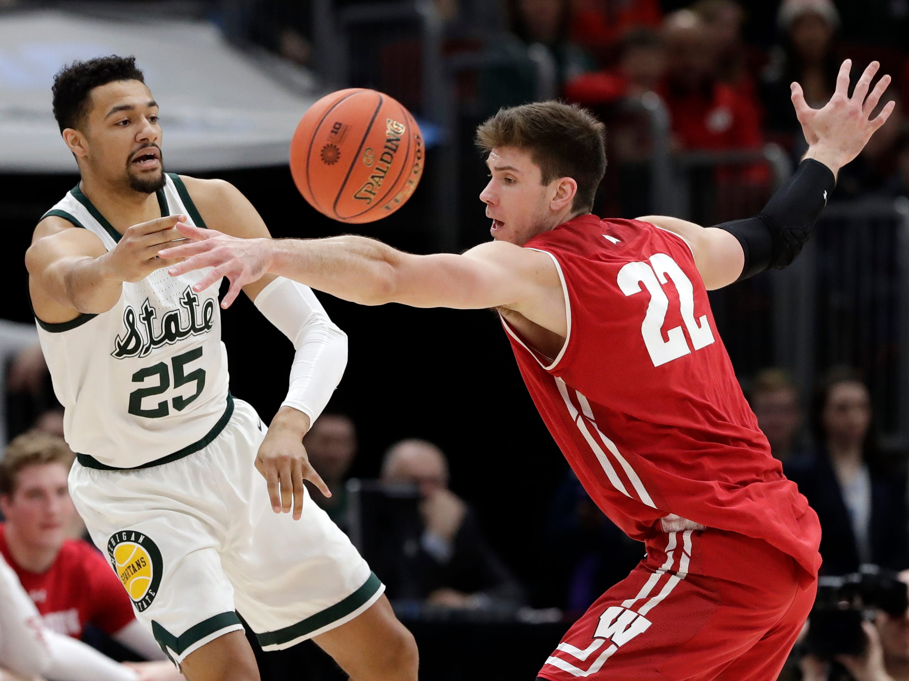 Michigan State's Kenny Goins passes the ball around Wisconsin's Ethan Happ during the first half.