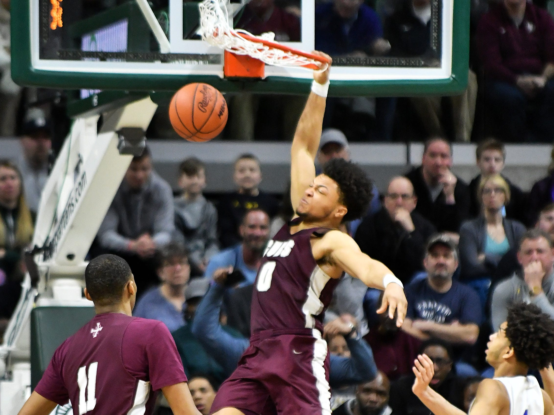 U-D Jesuit's Daniel Friday (0) dunks in the second half.   Y