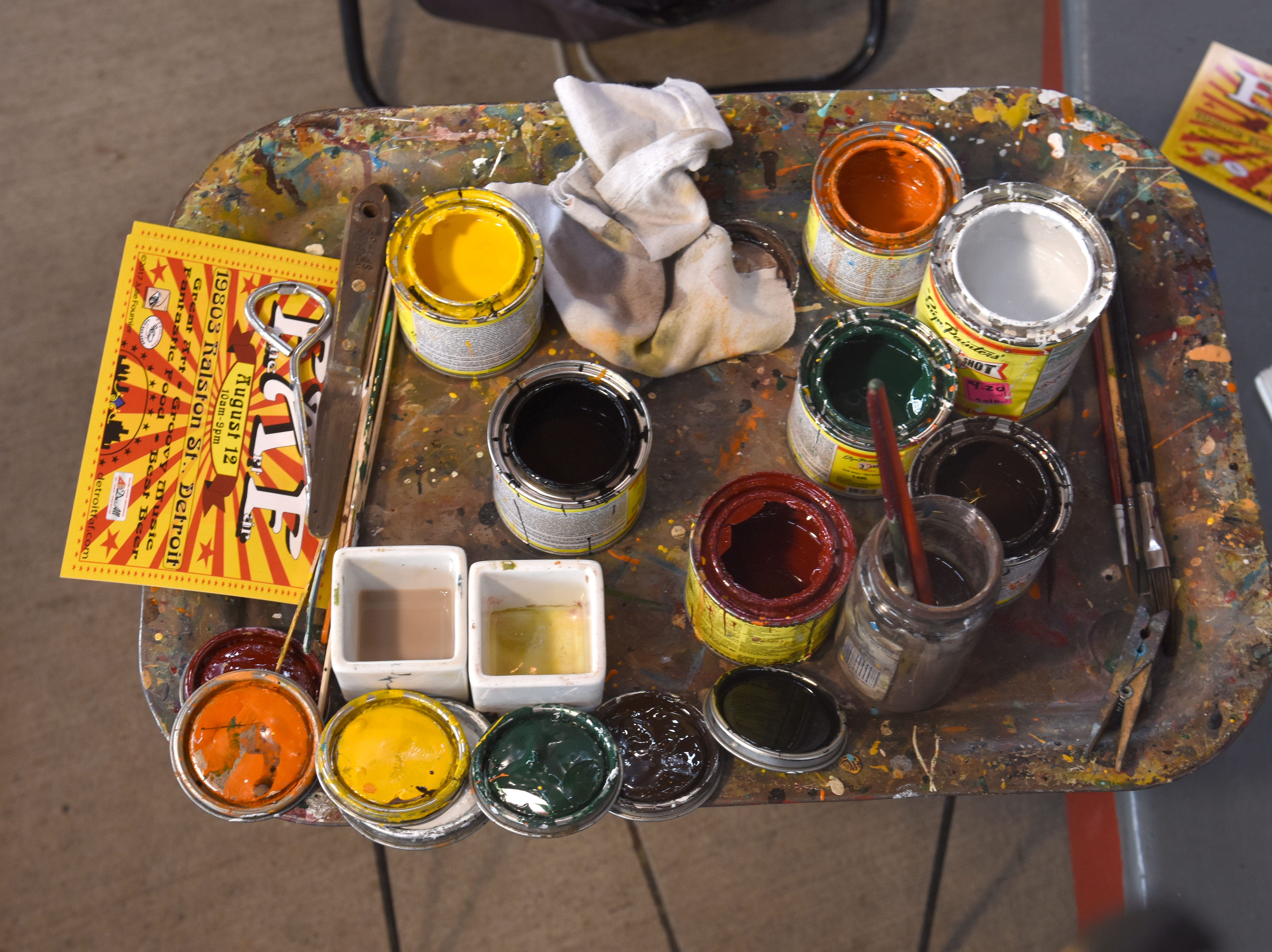 Small paint cans are part of Julie Fournier's palette of colors during there restoration of carousel figures.