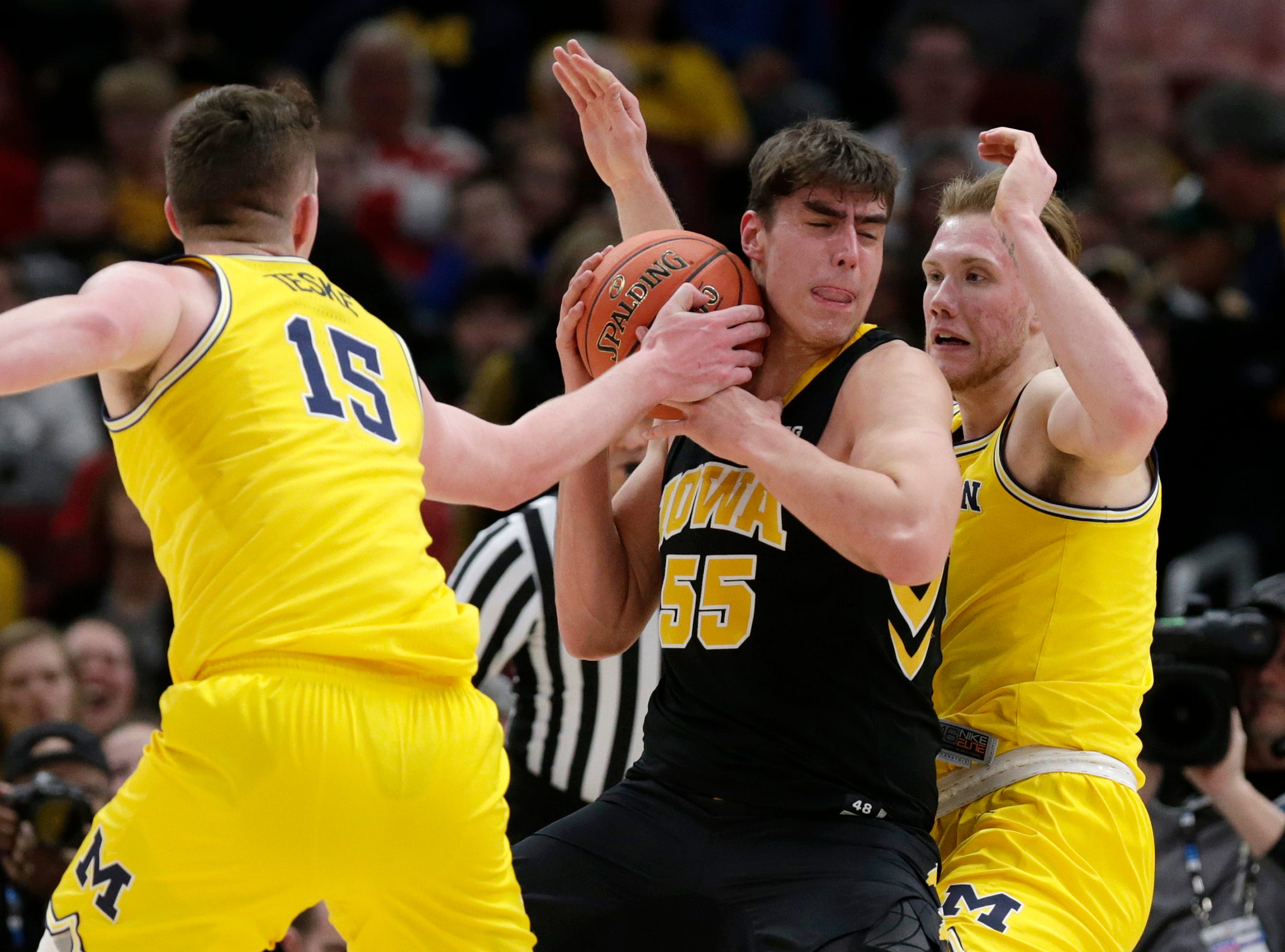 Iowa's Luka Garza (55) battles for the possession of the ball against Michigan's Jon Teske (15) during the first half.