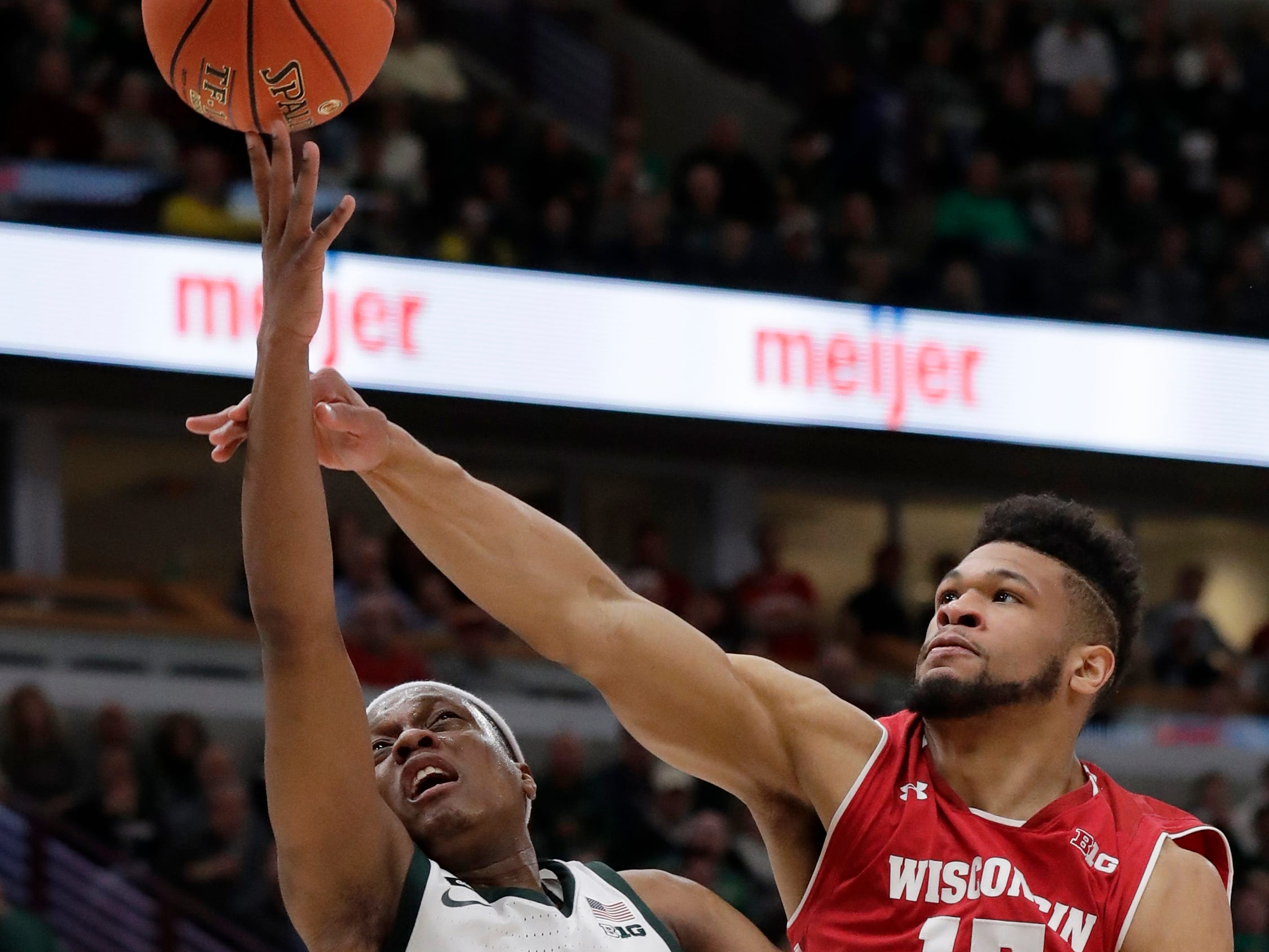 Michigan State's Cassius Winston shoots against Wisconsin's Charles Thomas IV during the second half.