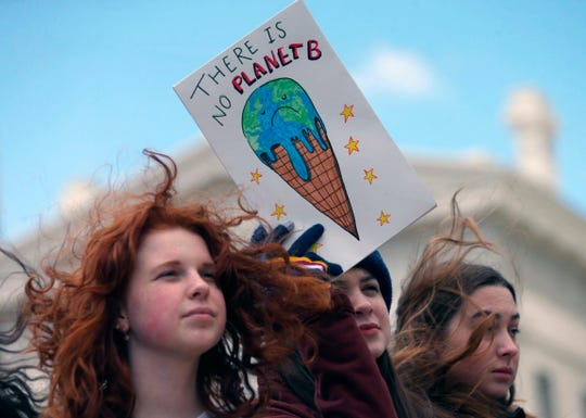 Adler Bowman, left, a student a Kirkwood High School, and schoolmates Sarah Nash, center, and Lizzie Stobbe protest for climate change, Friday, March 15, 2019, in St. Louis. S