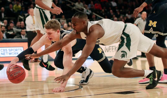 Michigan forward Moritz Wagner, left, and Michigan State guard Joshua Langford dive for a loose ball in the Big Ten semifinals last year.