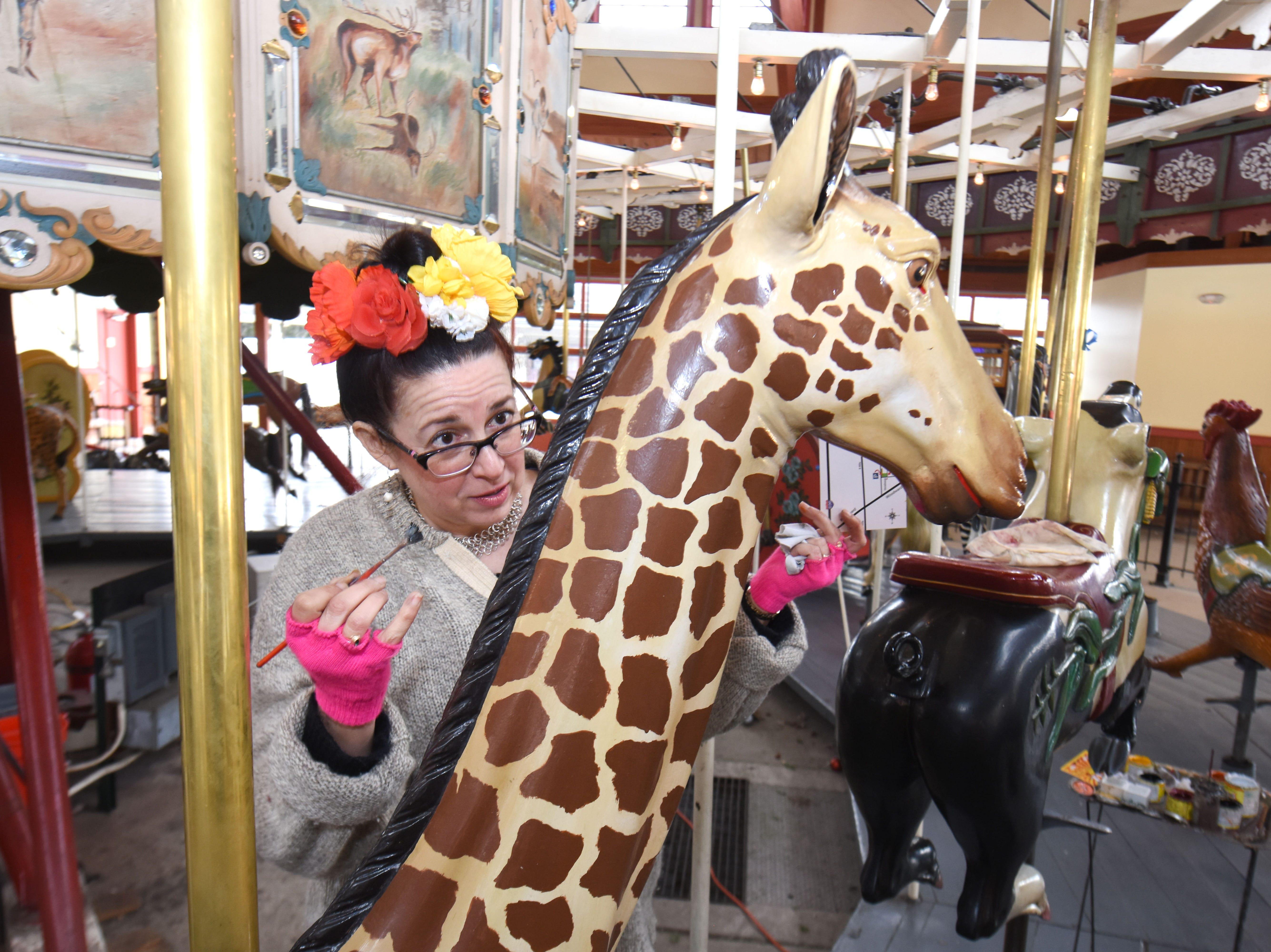 Julie Fournier works on the restoration of a giraffe figure at Greenfield Village in Dearborn.