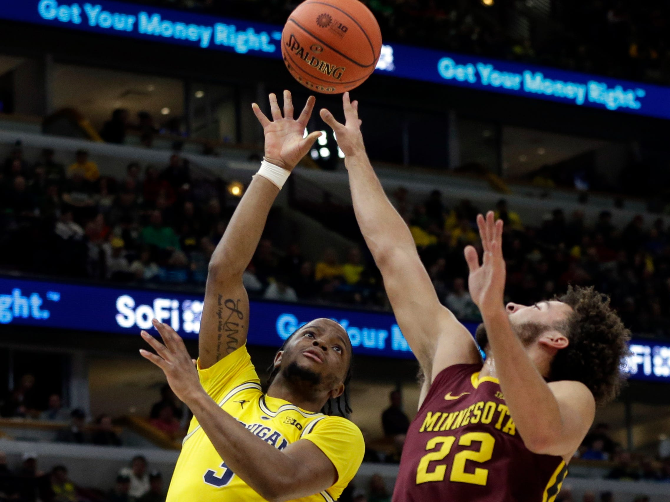 Michigan's Zavier Simpson takes a shot over Minnesota's Gabe Kalscheur during the first half.