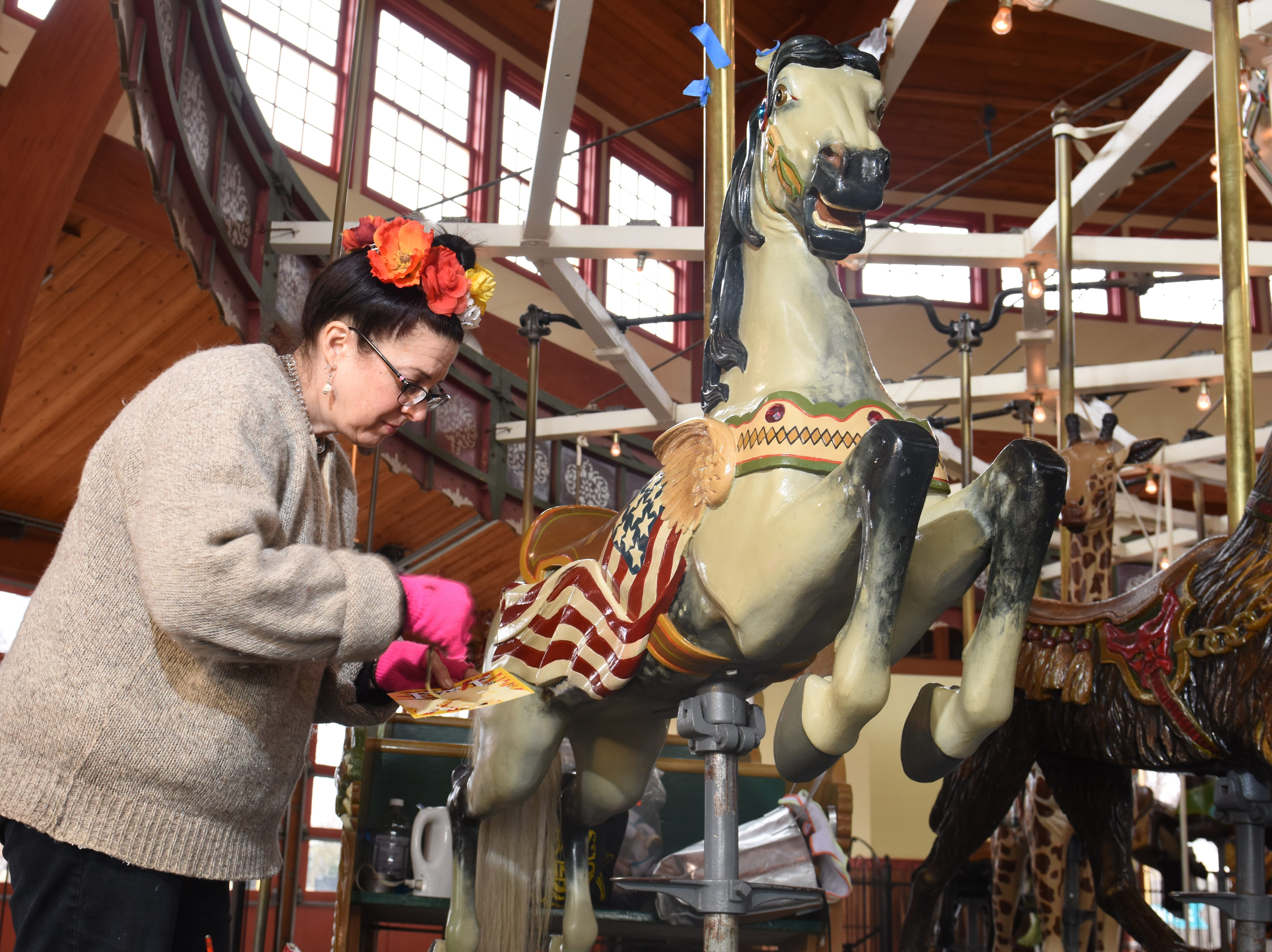 Julie Fournier paints one of the many carousel horse's with an American flag on it's rear quarter at Greenfield Village.