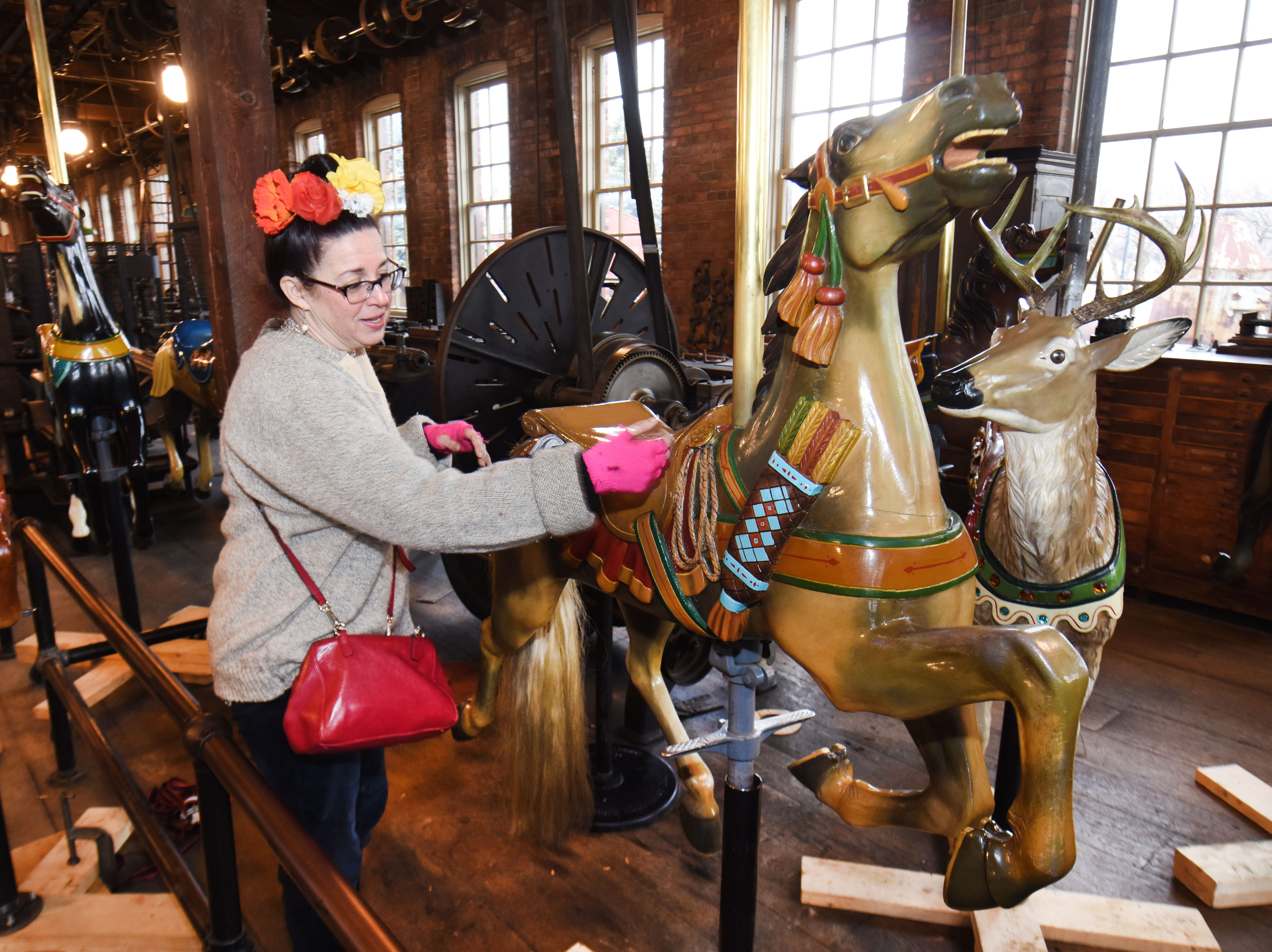 Julie Fournier, historic restoration artist,  looks at one of the many carousel horses as she works on at Greenfield Village's Armington & Sims machine shop.