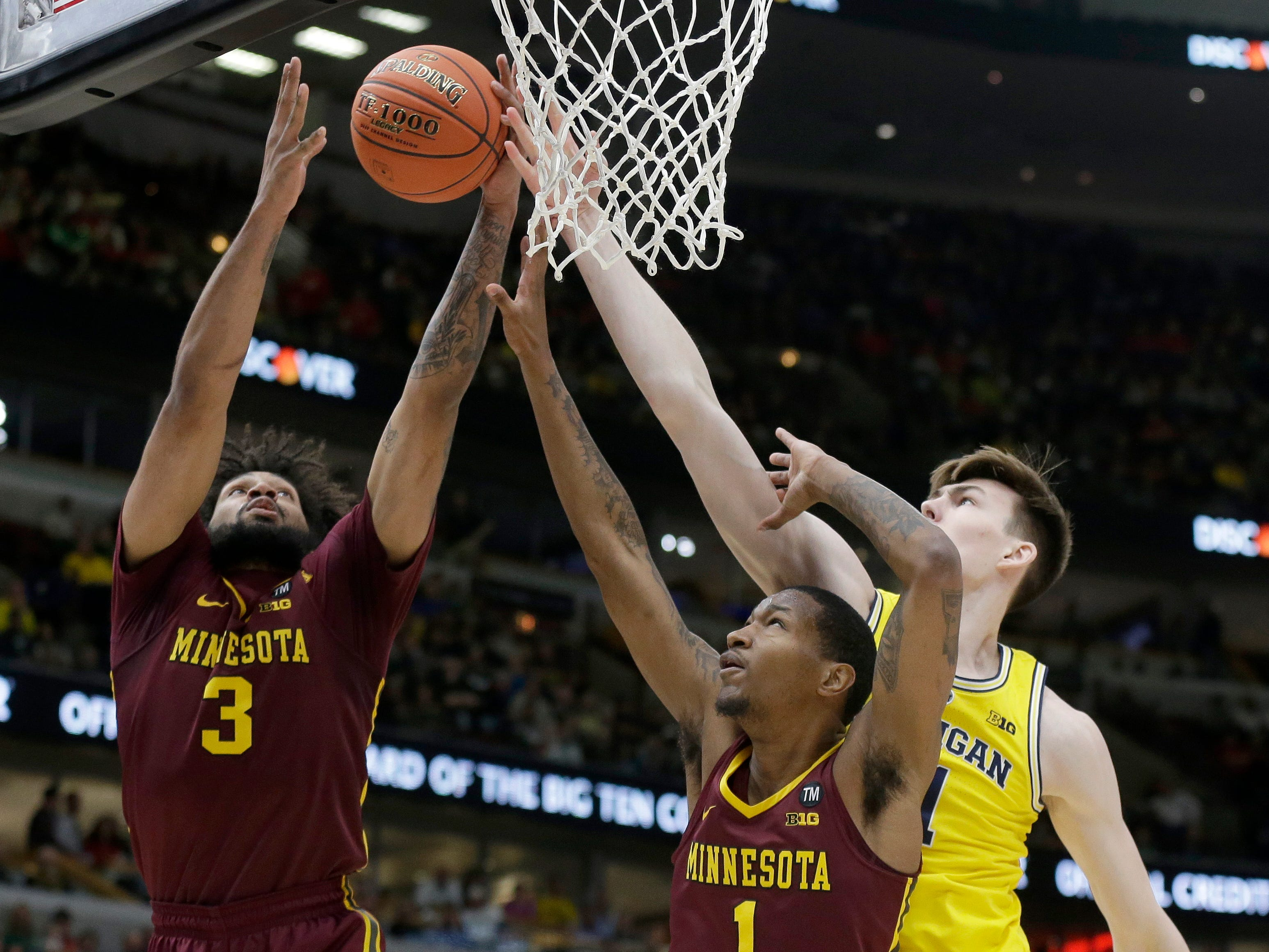 Minnesota's Jordan Murphy (3) and Dupree McBrayer and Michigan's Colin Castleton battle for a rebound during the first half.