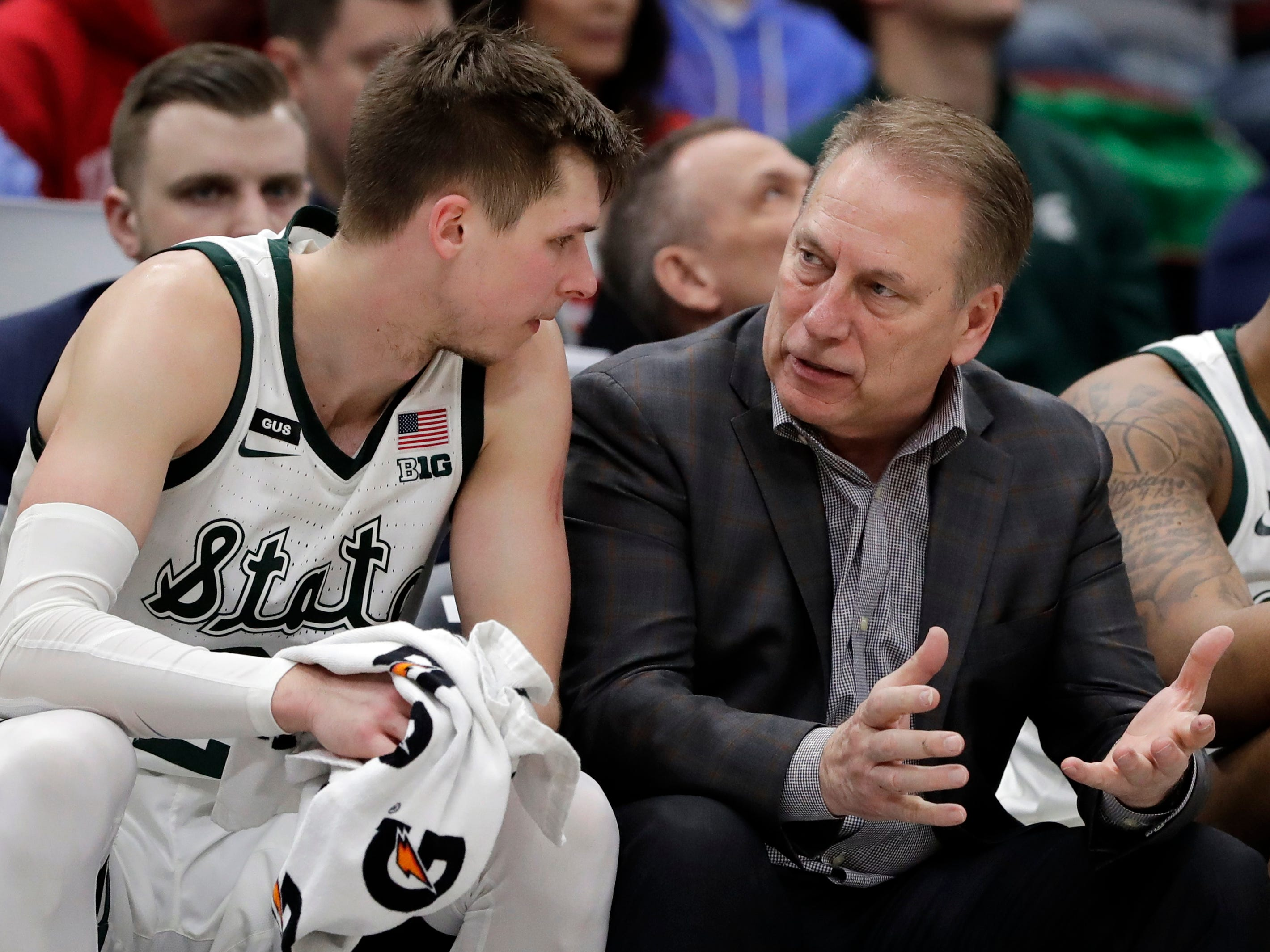 Michigan State head coach Tom Izzo talks to Matt McQuaid on the bench during the second half.