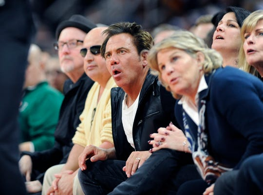 Pistons owner Tom Gores, center, keeps his eyes on the action in the second quarter.