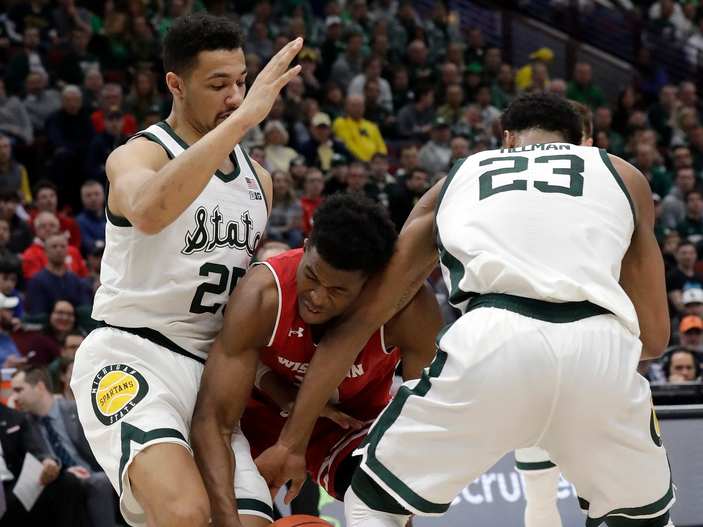 Wisconsin's Khalil Iverson goes after a loose ball against Michigan State's Kenny Goins (25) and Xavier Tillman during the first half.
