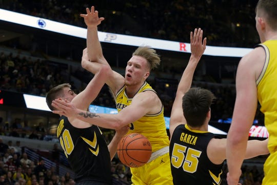 Michigan's Ignas Brazdeikis is fouled by Iowa's Joe Wieskamp (10) during the first half.