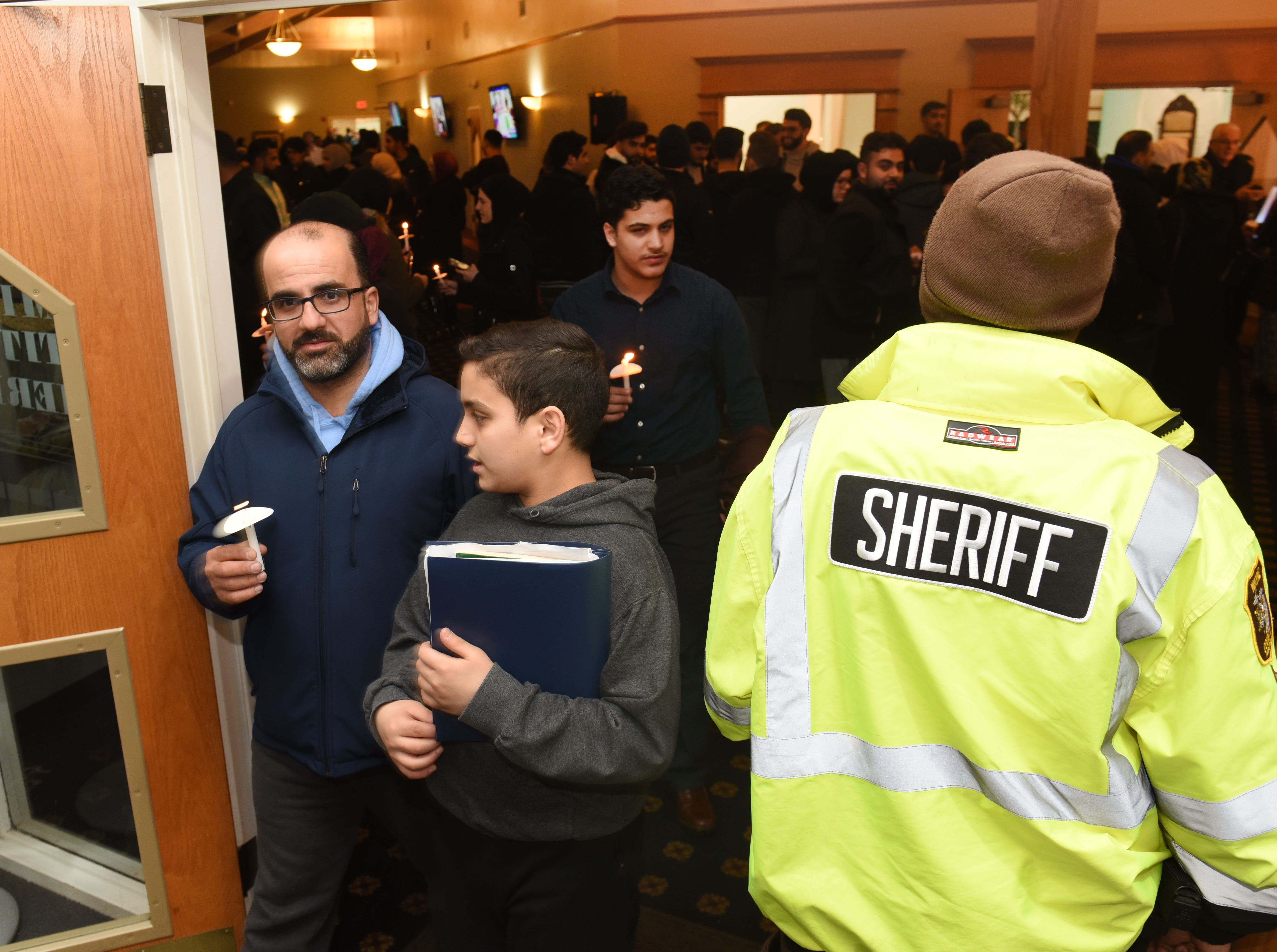A Wayne County Sheriff stands at the entrance to the Islamic Institute of America as local Muslims hold a vigil in remembrance of the lives lost in New Zealand.