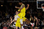Michigan's Charles Matthews, front, celebrates with Zavier Simpson after scoring a 3-point basket during the first half.
