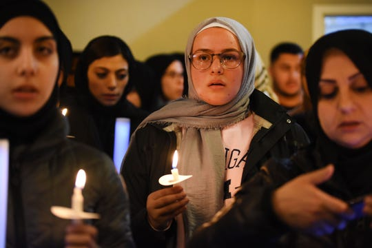 Hanna Jamel holds a candle in prayer at the Islamic Institute of America in Dearborn Heights during a prayer vigil in remembrance of the lives lost in a hate-motivated mass murder attack in New Zealand.