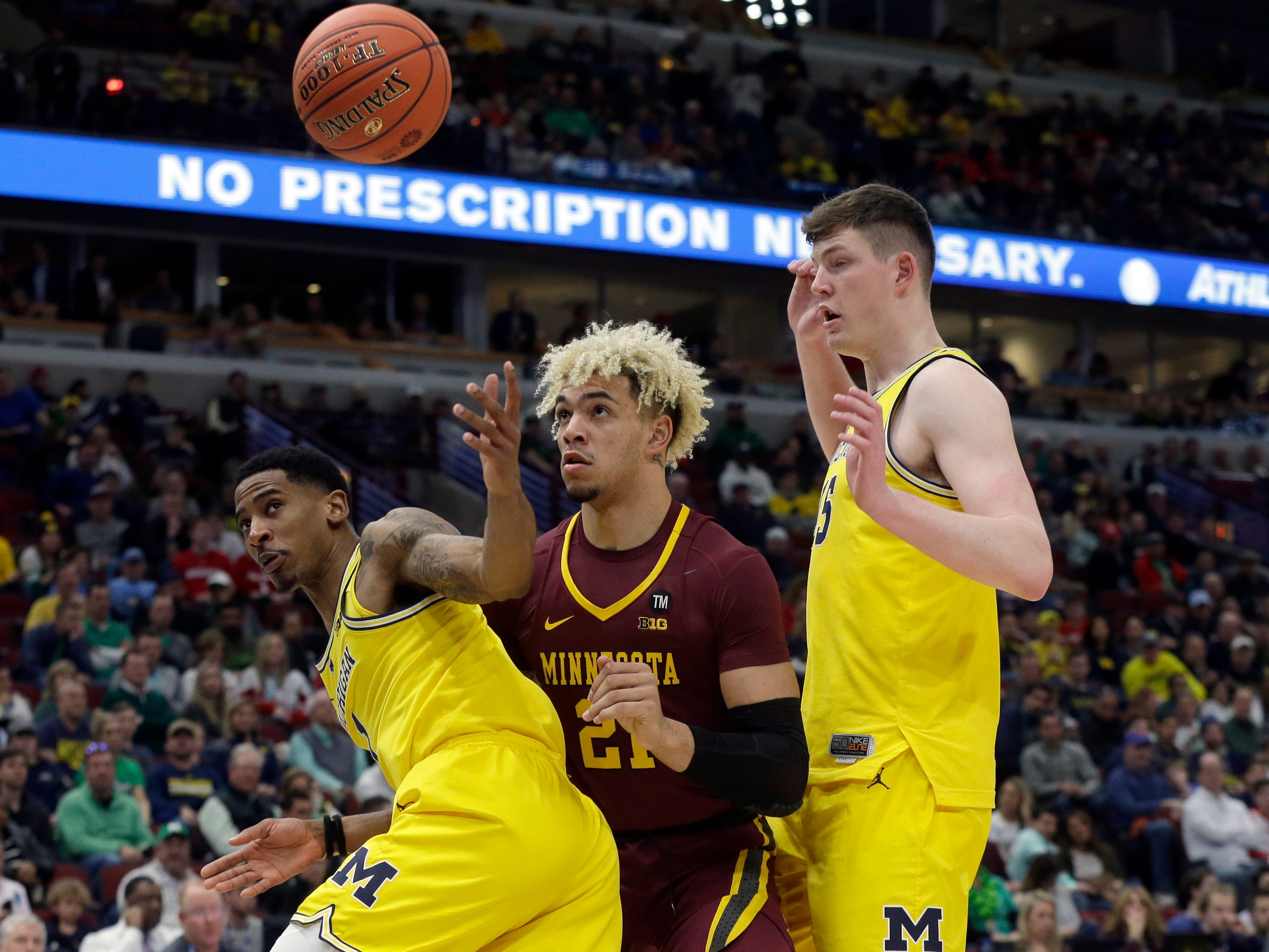From left, Michigan's Charles Matthews, Minnesota's Jarvis Omersa and Michigan's Jon Teske look for the loose ball during the second half.