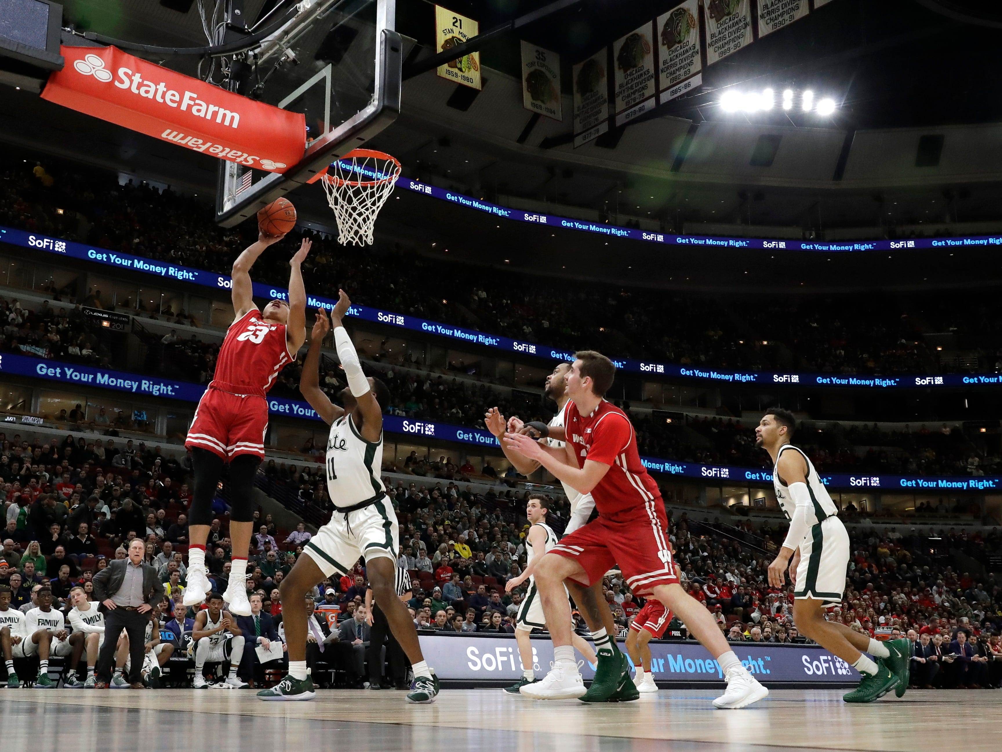 Wisconsin's Kobe King shoot over Michigan State's Aaron Henry during the first half.