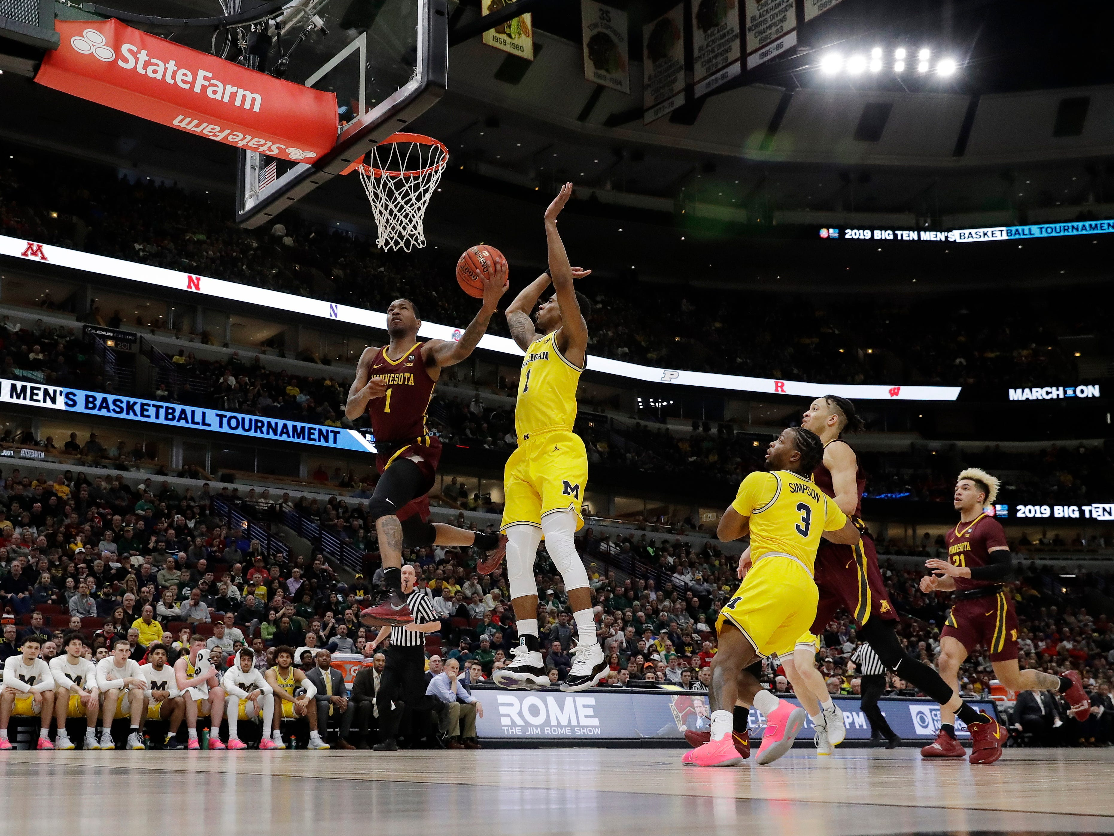 Minnesota's Dupree McBrayer, left, goes up for a basket against Michigan's Charles Matthews during the first half.