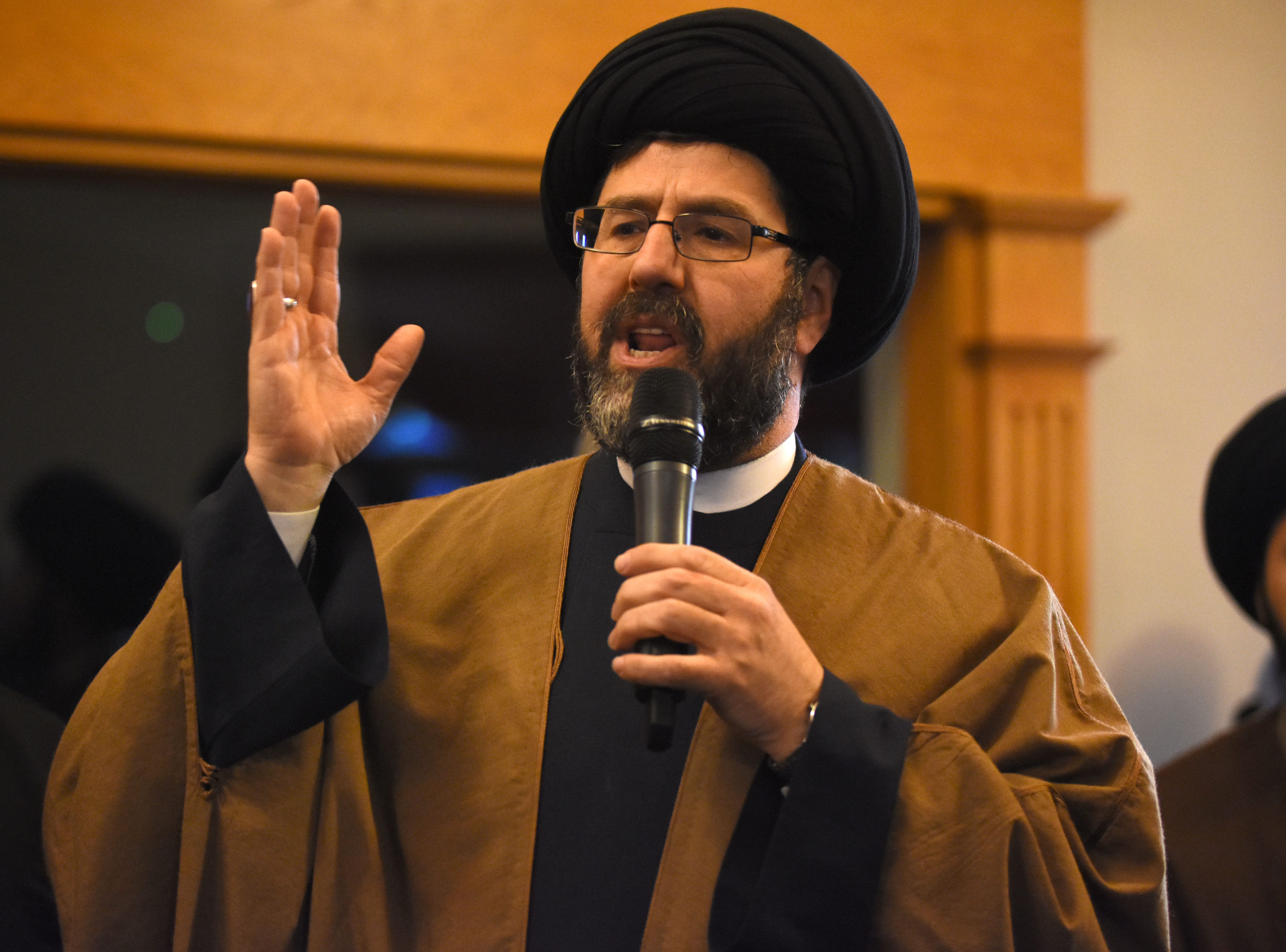 Sayed Hassan Qazwini speaks during a candle light prayer vigil at the Islamic Institute of America in Dearborn Heights Friday.