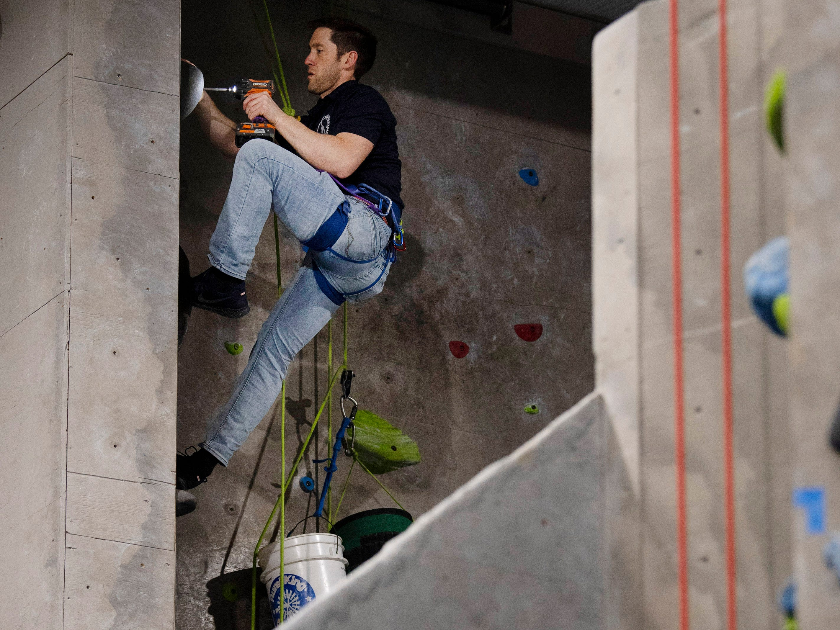 Brian Kennedy, director of operations, moves climbing holds at Vertical eXcape at 1315 N. Royal Avenue in Evansville Friday evening. The color-coded hand and foot holds are regularly modified to keep the experience fresh for climbers.