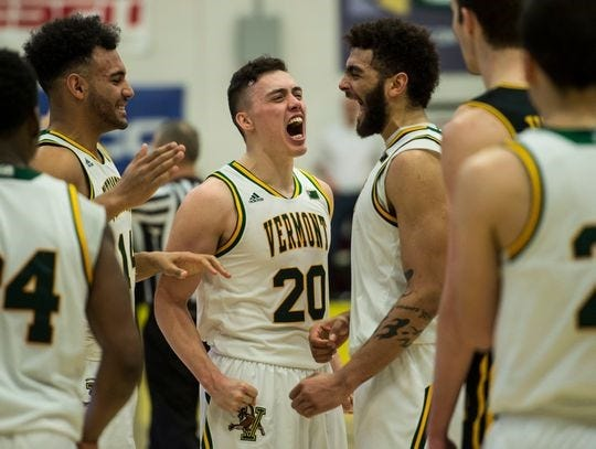Ernie Duncan (20) and his Vermont teammates celebrate after the Catamounts beat UMBC to secure an NCAA tournament berth.