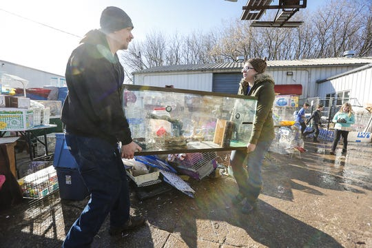 On Saturday. Tyler Alexander and Heather Rogers carry an aquarium out of Head To Tail Pet Supplies on Satterlee Street in Fond du Lac. The business was flooded when ice jams on the east branch of the Fond du Lac River and heavy rain caused widespread flooding problems in the city on Thursday.