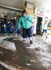 Cathy Wagner volunteers to help clean flood damage Saturday at Head To Tail Pet Supplies on Satterlee Street in Fond du Lac. Ice jams on the east branch of the Fond du Lac River and heavy rain caused widespread flooding problems in the city on Thursday.