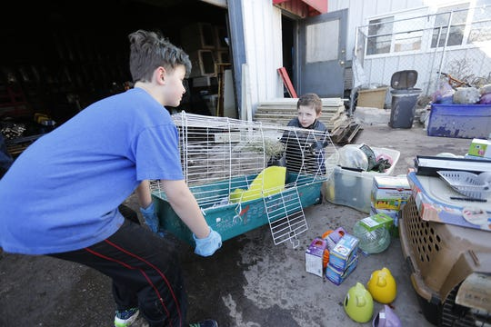 AJ Miller and Gage Scholl volunteer to help clean flood damage Saturday at Head To Tail Pet Supplies on Satterlee Street in Fond du Lac. Ice jams on the east branch of the Fond du Lac River and heavy rain caused widespread flooding problems in the city on Thursday.
