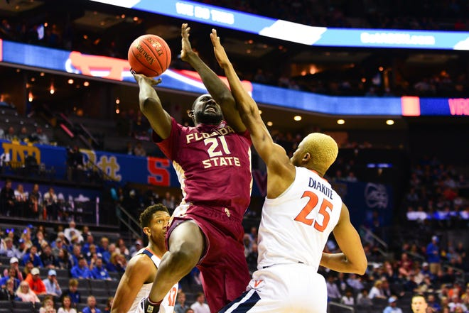 Florida State senior center Christ Koumadje powers through Virginia redshirt junior forward Mamadi Diakite during the first half of the ACC Tournament Semifinals at the Spectrum Center in Charlotte on Friday.
